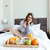 pretty smiling woman sitting on bed and having breakfast stock photo © deandrobot
