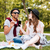smiling couple listening to music from cell phone on picnic stock photo © deandrobot