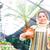 smiling female gardener holding small palm in pot and shovel stock photo © deandrobot