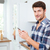 happy young man using cell phone on the kitchen stock photo © deandrobot