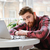 bearded young man sitting in cafe while using laptop computer stock photo © deandrobot