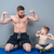 smiling shirtless dad and son showing biceps sitting on mat stock photo © deandrobot