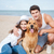young attractive couple with a dog sitting on the beach stock photo © deandrobot