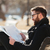 Smiling man in glasses reading newspaper on the bench outdoors stock photo © deandrobot