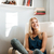 cheerful woman sitting in armchair at home stock photo © deandrobot