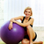 young happy fit woman sitting on the yoga mat with fitball stock photo © deandrobot