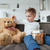 Little boy sitting on sofa with teddy bear at home stock photo © deandrobot