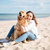 happy woman sitting and hugging her dog on the beach stock photo © deandrobot