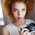 beautiful redhead curly young woman photographer with vintage camera stock photo © deandrobot