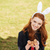 portrait of a smiling red head woman wearing bunny ears stock photo © deandrobot