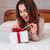 woman opening present box while lying in bed at home stock photo © deandrobot