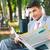 üzletember · ül · pad · újság · mosolyog · másfelé · néz - stock fotó © deandrobot