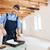 smiling builder using paint roller indoors stock photo © deandrobot