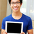 young smiling asian man showing blank tablet computer screen at home stock photo © deandrobot
