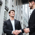 two cheerful young businessmen shaking hands stock photo © deandrobot