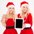 smiling women in santa cloth showing tablet computer screen stock photo © deandrobot