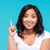 happy inspired vietnamese woman pointing up and having an idea stock photo © deandrobot