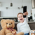 Happy boy sitting with teddy bear at home watching tv stock photo © deandrobot