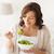 smiling young woman eating salad at home stock photo © dolgachov