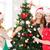 women in santa helper hats decorating a tree stock photo © dolgachov