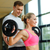smiling man and woman with barbell in gym stock photo © dolgachov