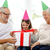 smiling family in party hats with gift box at home stock photo © dolgachov