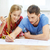 smiling couple looking at blueprint at home stock photo © dolgachov