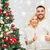 happy couple showing thumbs up with christmas tree stock photo © dolgachov