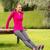 smiling woman doing push ups on bench outdoors stock photo © dolgachov