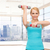 smiling woman with dumbbells flexing biceps in gym stock photo © dolgachov