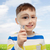 happy little boy looking through magnifying glass stock photo © dolgachov