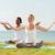 smiling couple making yoga exercises outdoors stock photo © dolgachov