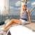 smiling young woman sitting on yacht deck stock photo © dolgachov