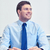 smiling businessman sitting in office stock photo © dolgachov