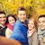 group of smiling men and women in autumn park stock photo © dolgachov