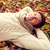 close up of smiling young man lying in autumn park stock photo © dolgachov