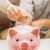 close up of hands putting coin money to piggy bank stock photo © dolgachov