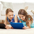 happy girls with tablet pc lying on floor at home stock photo © dolgachov