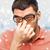 close up of tired man in eyeglasses rubbing eyes stock photo © dolgachov