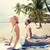 happy couple making yoga exercises on beach stock photo © dolgachov