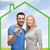 smiling couple holding key over green house stock photo © dolgachov