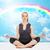 happy young woman meditating in yoga lotus pose stock photo © dolgachov
