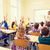 group of school kids raising hands in classroom stock photo © dolgachov