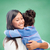 happy woman and little girl hugging at school stock photo © dolgachov