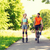 happy couple with roller skates and bicycle riding stock photo © dolgachov