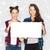 smiling teenage girls holding white blank board stock photo © dolgachov