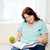 plus size woman with book and apple at home stock photo © dolgachov