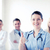 doctor with group of medics showing thumbs up stock photo © dolgachov