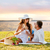 happy couple drinking champagne on picnic stock photo © dolgachov