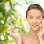 happy young woman applying cream to her face stock photo © dolgachov